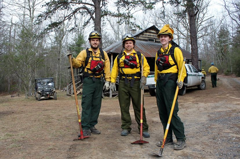 Three people pose together in front of a rustic cabin. They are wearing yellow fire retardant gear and holding long handled hoes. A white pickup truck is parked behind them.