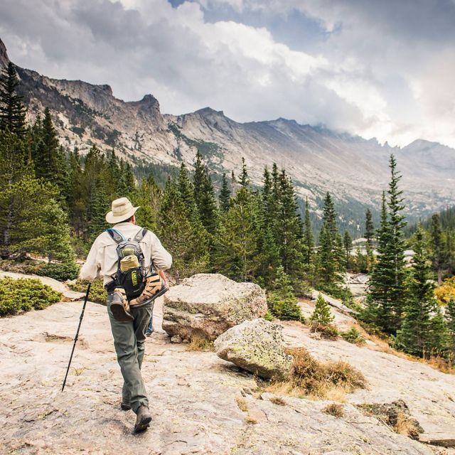 A park visitor hiking up to Mills Lake in Rocky Mountain National Park.