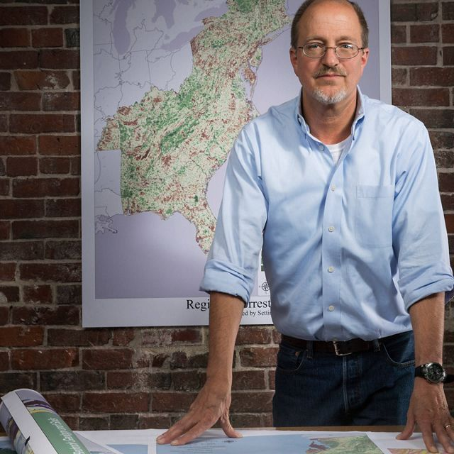 Photo of Dr. Mark Anderson, standing in front of maps.