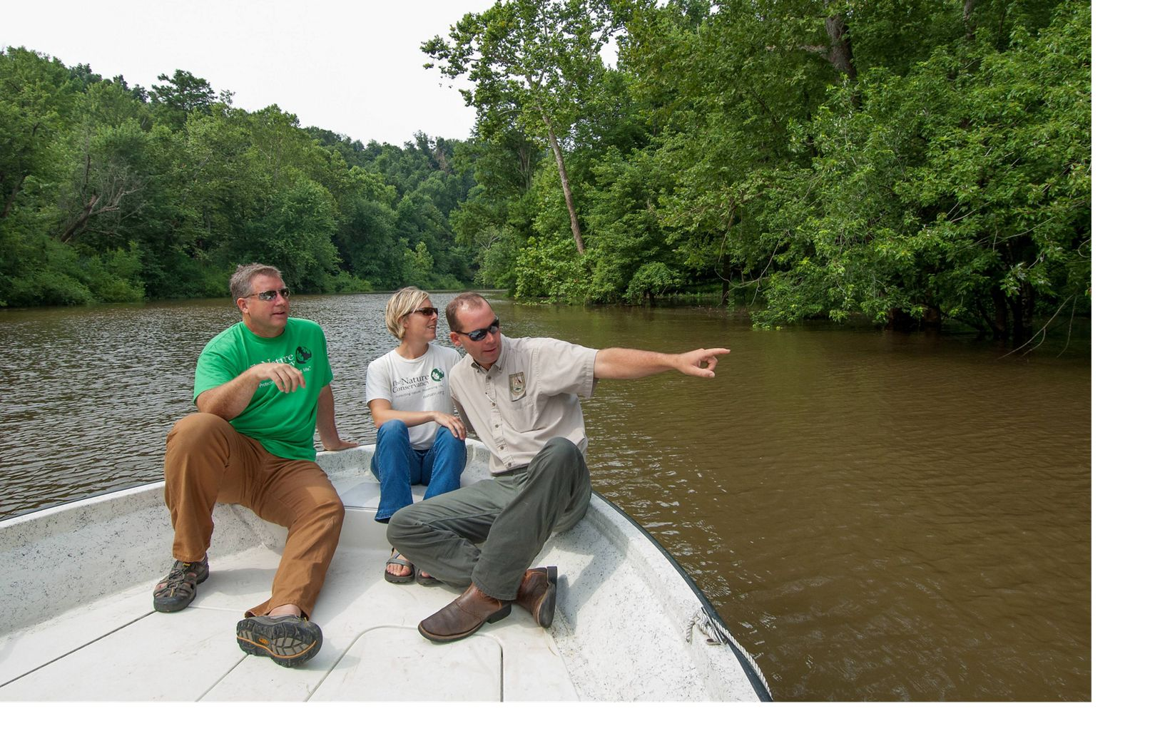 Using a small boat to navigate along the banks of the Ohio and Tradewater Rivers, staff from The Nature Conservancy and the Kentucky Department of Fish and Wildlife tour the Big Rivers  Phase II project located at the confluence of the two rivers in Crittenden County, Kentucky. The project will protect 4,285 acres providing watershed and water quality protection as well as guarding endangered, threatened and rare species recovery. Photographed from left to right; Terry Cook (the Conservancy's Kentucky State Director), Shelly Morris (Western Kentucky Project Director for the Conservancy), and Curt Devine (with the Kentucky Department of Fish and Wildlife).