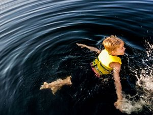 Photo of a boy swimming in water.