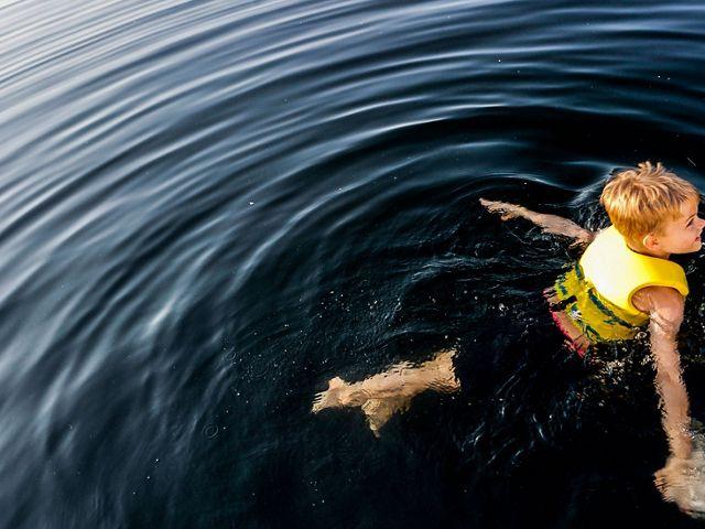 Boy enjoys a lake swim