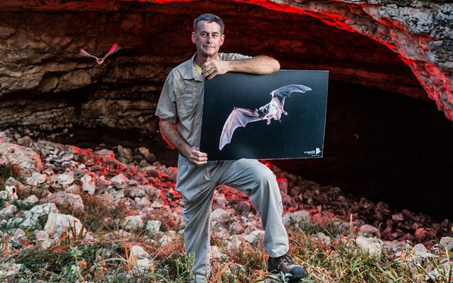 A man holds a photo of a bat outside the entrance of a cave