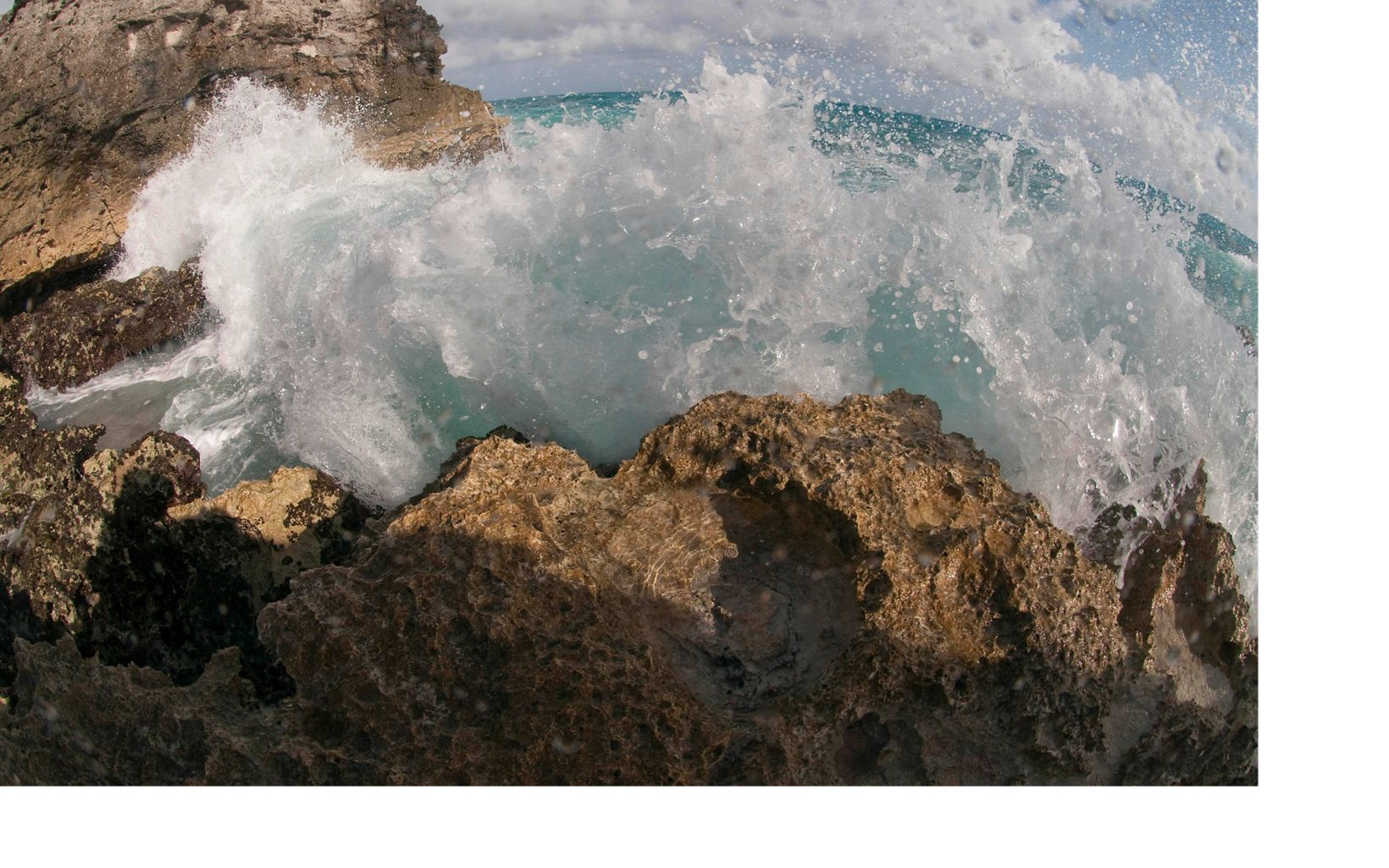Water splashes against the rocky shore.