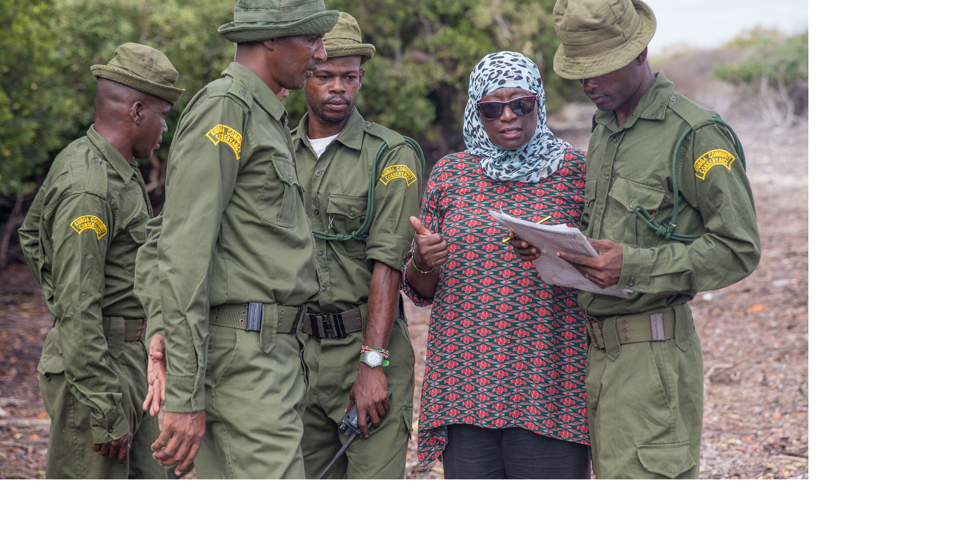 a woman talking to a group of men in military uniform.
