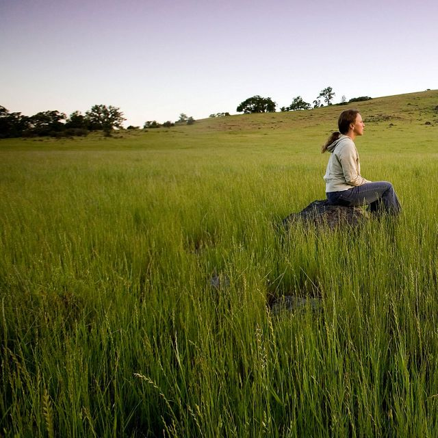 A female hiker pauses to view the lush grasslands and blue oak woodlands that characterize Dye Creek Preserve and Canyon