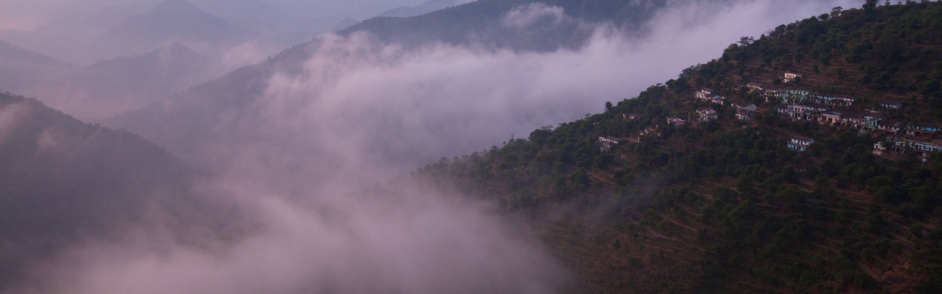 The morning clouds and fog lift off the small towns in the lower Himalaya mountains.