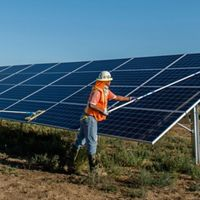 Workers clean solar panels.