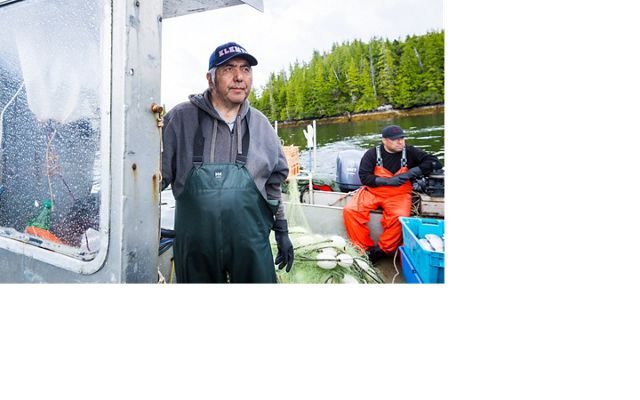 Ernest (Charlie) Mason with son, Ernie Mason (backgroung) looks for jumping salmon in the Kitasoo Bay, a sign that there is a larger school to be caught under the surface. Cha