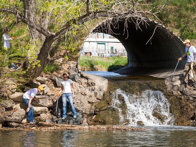 Volunteers pick up trash using grabbers, while standing near a stream and a large culvert.