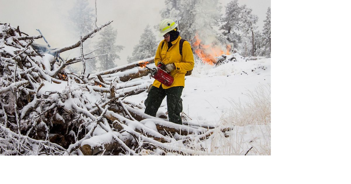 A fireworker burns brush piles that have been cut to reduce wildfire risk and protect clean water in the Denver, Colorado, area.