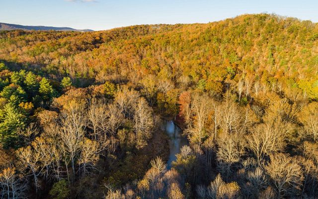 A small section of Sideling Hill Creek is visible as it curves through a thick forest. The leaves are in late fall color.