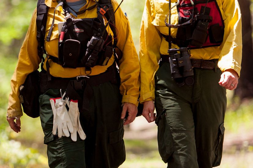 Two women wearing yellow fire retardant gear walk together down a wide dirt path in a TNC preserve during a controlled burn. They both wear red vests holding walkie-talkies.