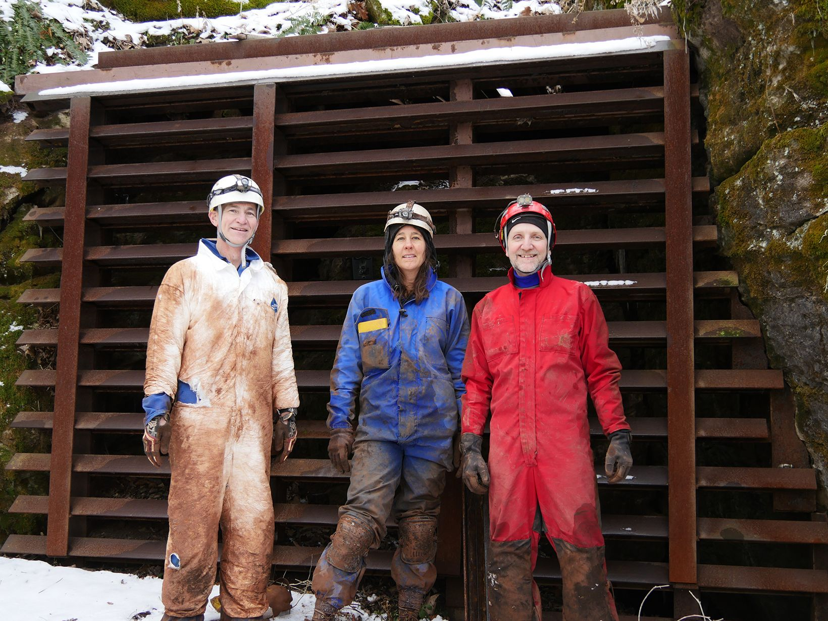 Three people stand together in front of a metal barrier at the opening to a cave. They wear coveralls covered in mud and ripped in places where they had to crawl through narrow cave openings.