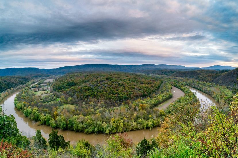 Looking down on a still brown river as it curves through a thick forest. A mountain ridgeline stretches across the horizon.