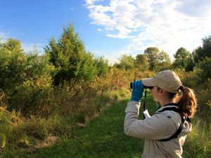 A woman with binoculars enjoys a morning bird walk.