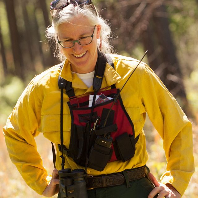 Candid photo of Senior Conservation Scientist Judy Dunscomb. She is standing in a forest wearing yellow fire gear with a red bib that hold communications gear.