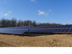 An array of solar panels stand in an open field