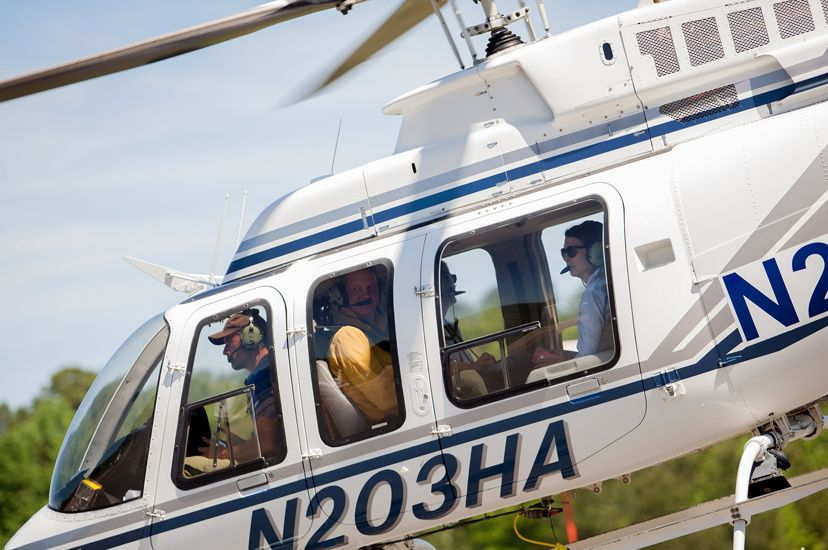 A white helicopter lifts off from a small airport. The pilot and three passengers are visible through the windows.