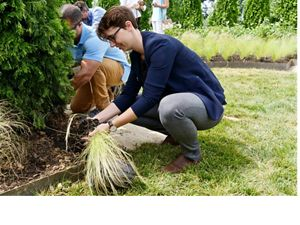 Lena Easton-Calabria places a plant during the dedication of a new memorial greenspace at Mount Olivet cemetery, Washington, D.C.