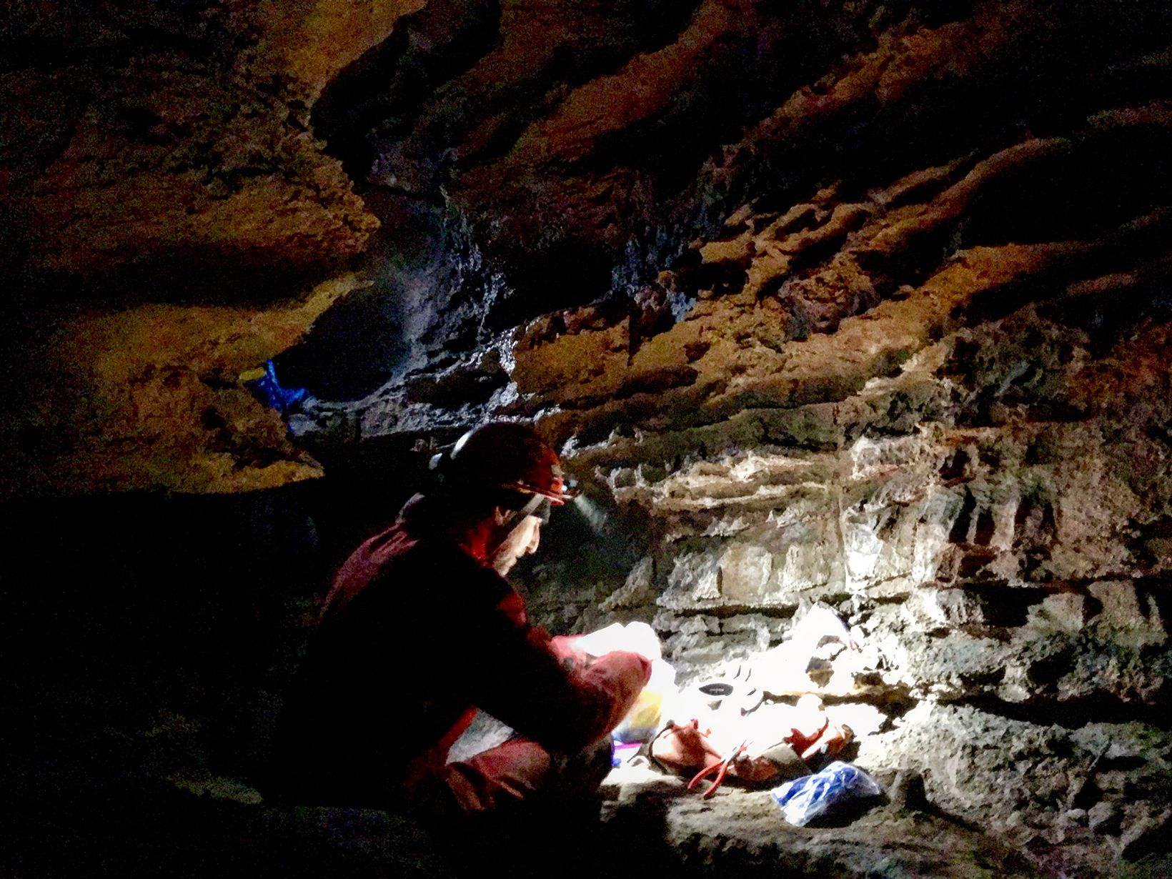 A man in an orange jumpsuit and hard hat crouches in a low cave preparing materials for a survey of the cave's bats. He uses his hat's headlamp to illuminate the pile of materials in front of him.