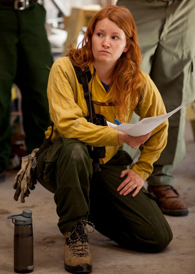 A woman with red hair kneels during a pre-burn briefing, listening intently to the information being shared.