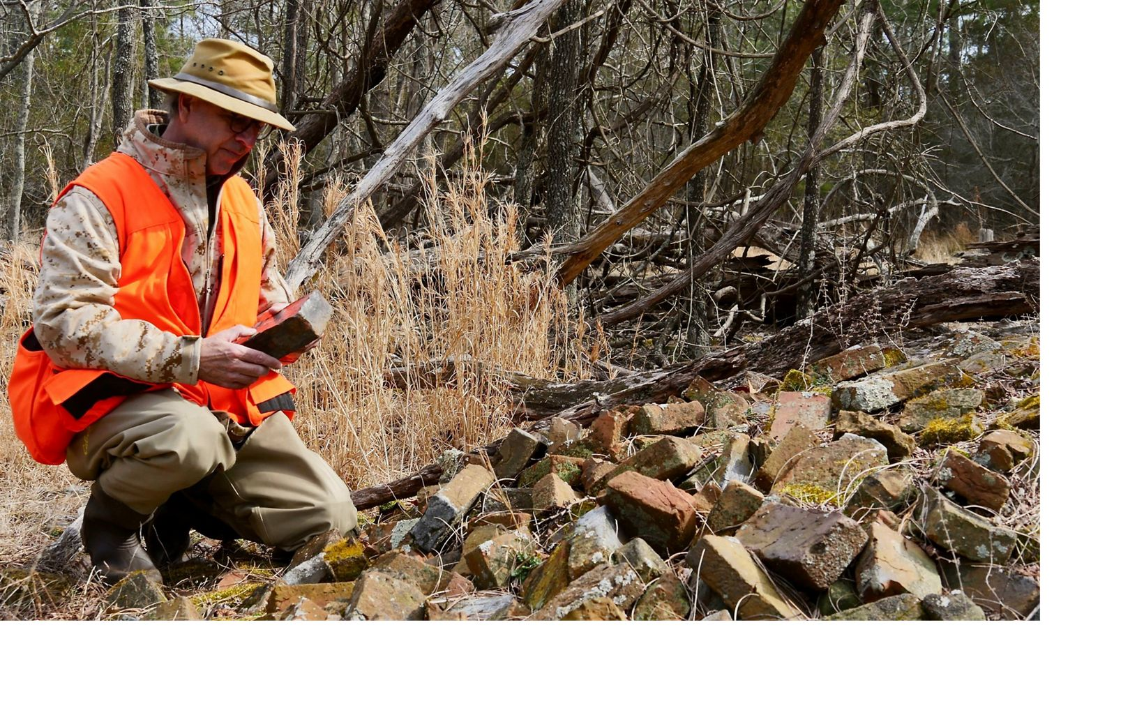 Joe Fehrer inspects bricks from the historic Robson family homestead on TNC's Robinson Neck preserve.