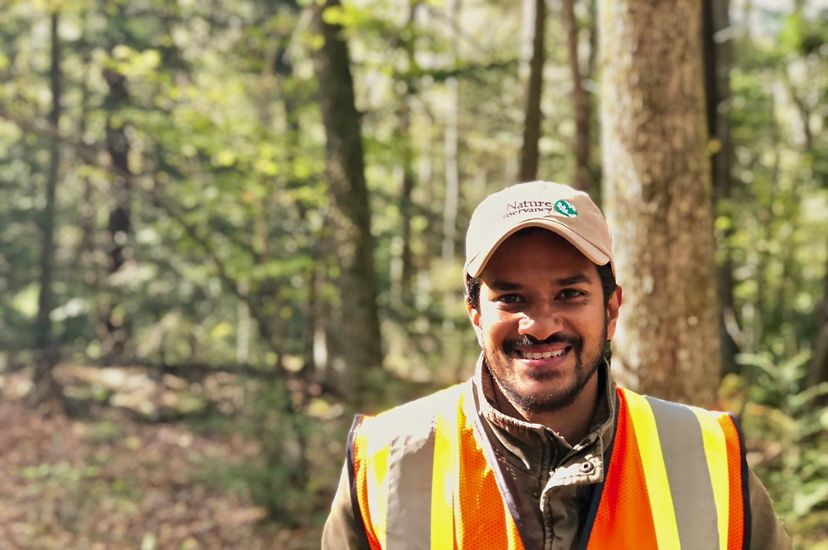 A smiling man wearing a ballcap and orange and yellow reflective vest stands in a forest.