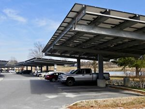 Car and trucks are parked in rows at a commuter parking lot. Large solar arrays spanning 6 or 7 parking spaces shade the vehicles while generating energy.