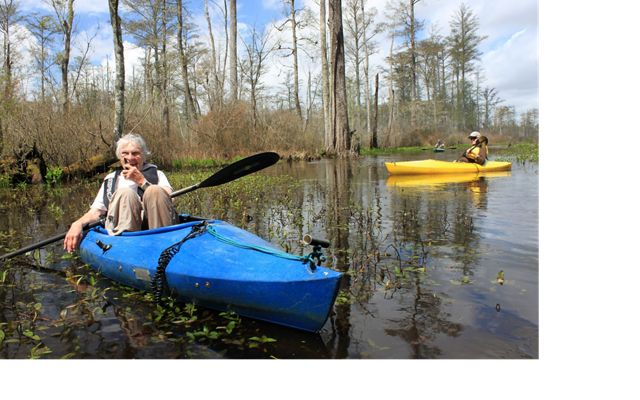 A smiling woman sits in a blue kayak floating in a cypress swamp. A man in a yellow kayak paddles behind her.
