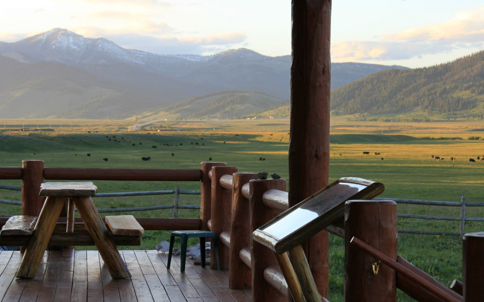 Log cabin porch with a picnic table and a view of cattle grazing in fields and snow-capped mountains in the distance.