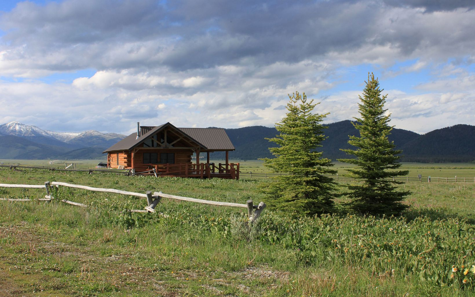 A modern log cabin with a wraparound deck stands in a flat grassland with snow-capped mountains in the distance.