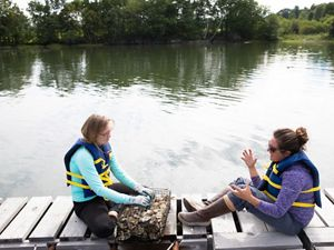 Two women have a discussion while sitting on a dock.