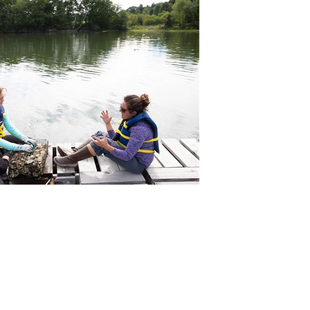 Alison Laferriere and TNC Oyster Conservation Coordinator, Amanda Moeser, sit on a dock near the Jackson Estuarine Laboratory in Durham, New Hampshire,  and talk about the best way to count the spat on oyster shells.