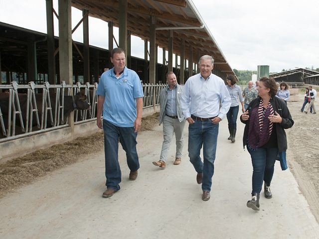 All Internal Rights. Jeremy Visser, left,  gives Governor Inslee, Jessie Israel (TNC), and others a tour around the dairy farm. Photo by Hannah Letinich.