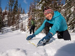 TNC staff visit a Snotel site, check time lapse camera status and measure snowpack.  Emily Howe measures snow depth at the perimeter of the snotel site.