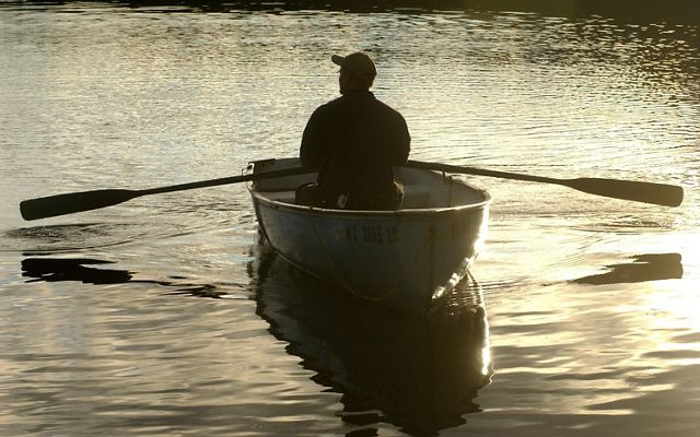 Silhouette of Deputy State Director Matt Dallman in a rowboat on tranquil waters at sunset at Tenderfoot Forest Reserve