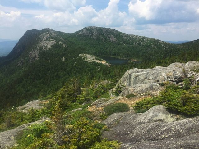 A rocky peak with shrubby green vegetation and a pond close to the summit.