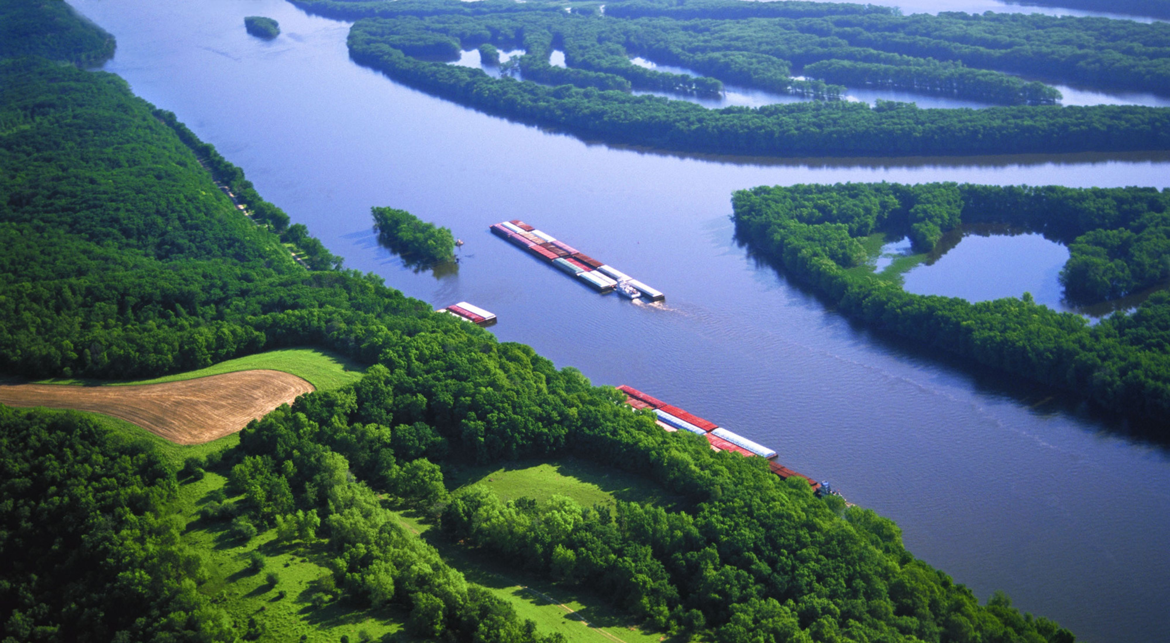 Aerial photo of the Mississippi River as barges navigate the water.