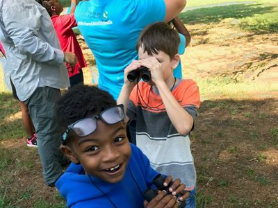 Two boys with binoculars at a summer nature camp. The boy in the background looks through the lenses. The boy in the foreground smiles up at the person taking the photo.