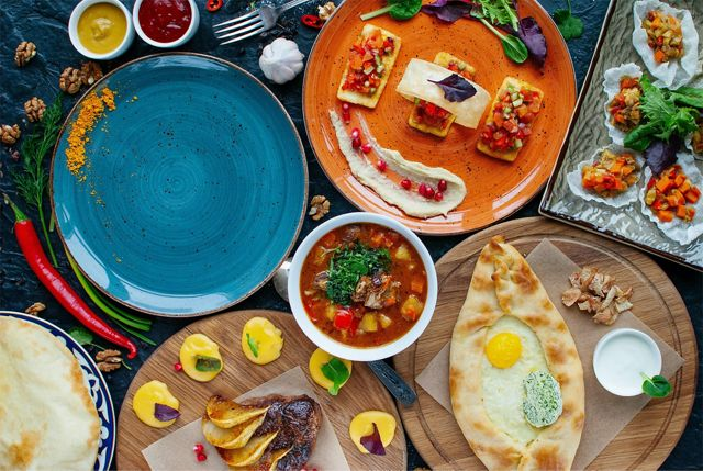 an overhead shot of a colorful table filled with plates of different types of food