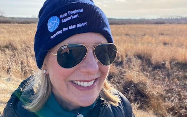 A woman in the sunshine wearing a New England Aquarium beanie