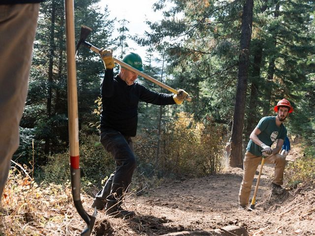 swings a tool while working on the first section of the new Towns to Teanaway trail system.