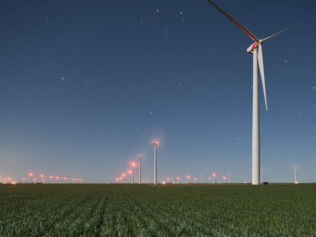 Lines of wind turbines in a green farm field.