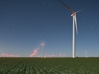 Wind turbines towering over agricultural field