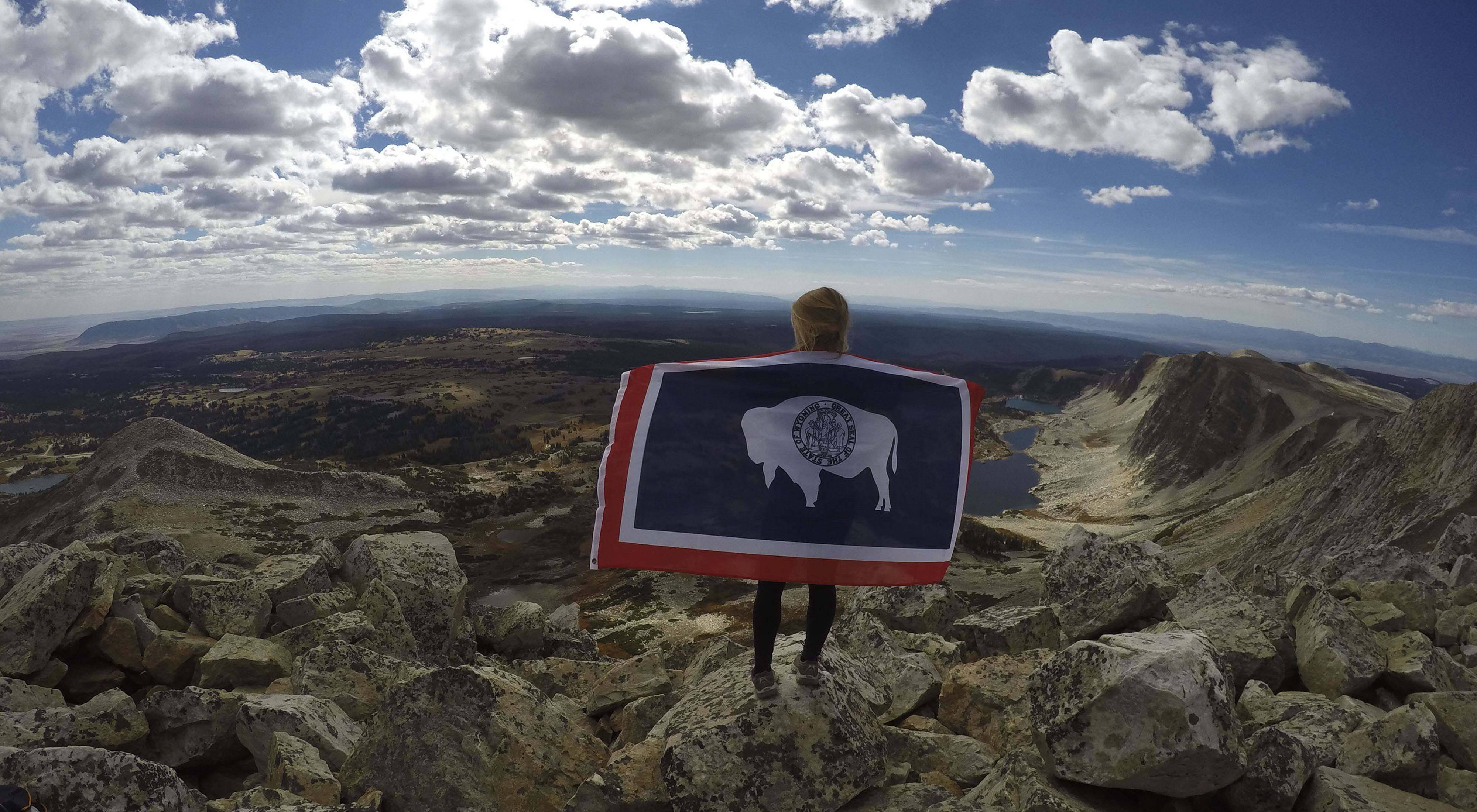 Young girl shows her Wyoming pride on top of a snow-capped peak.