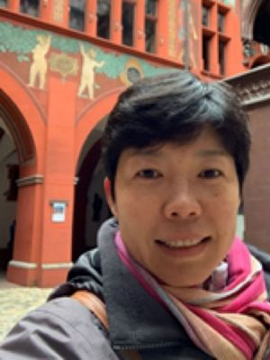 Selfie of Ying Li in front of a red building with murals painted on it.