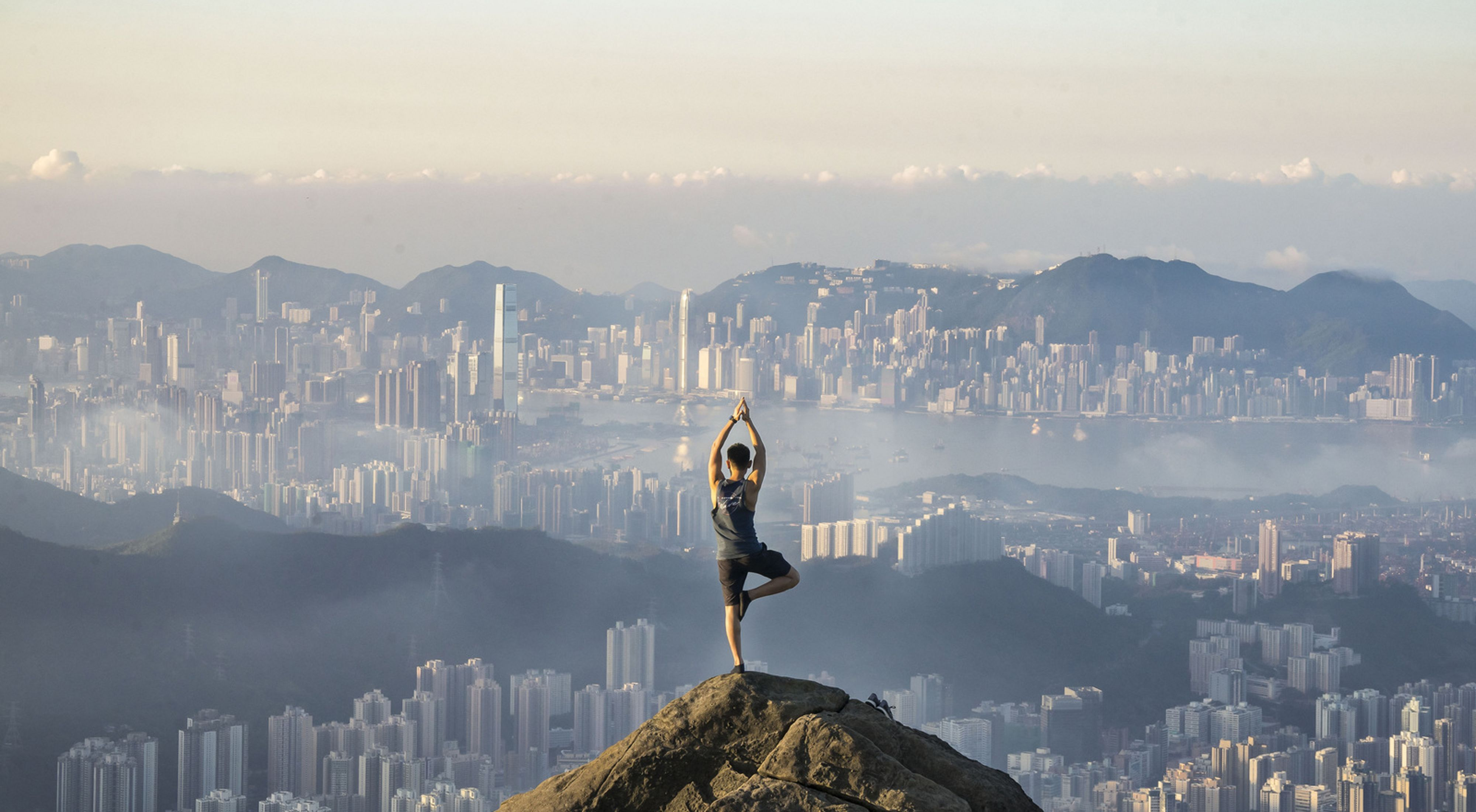 A person does yoga overlooking the skyline of Hong Kong.