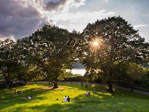 People enjoy the afternoon on the Billings Lawn of Fort Tryon Park along the Hudson River in Upper Manhattan, New York.